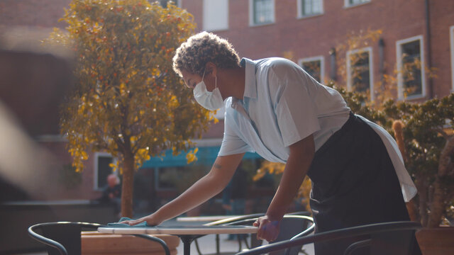 Portrait of african waitress wearing face mask cleaning table outdoors