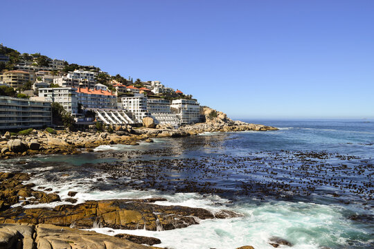 Rocks, the sea and buildings on the slope of the hill in Bantry Bay, Cape Town, South Africa.