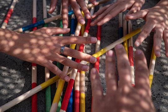 Cropped Hands Gesturing Over Sticks