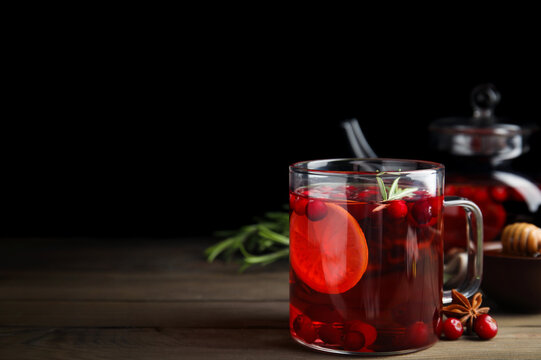 Tasty hot cranberry tea with rosemary and lemon on wooden table. Space for text