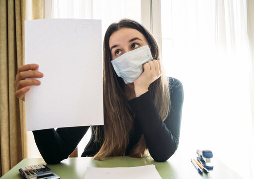 Young Woman Wearing Mask Holding Paper Against Window At Home