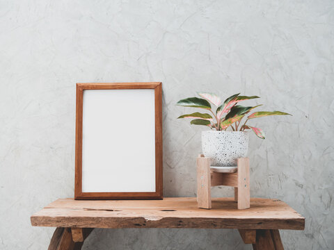 Teak wood frame mock up and Aglaonema houseplant(Chinese Evergreen) in modern white and black  ceramic container  on teak wood table with cement wall background with copy space for products