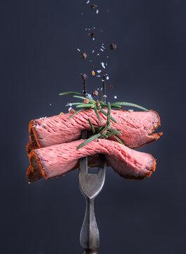 Peppered roast beef pastrami slices folded big fork and sprinkled with salt and pepper.