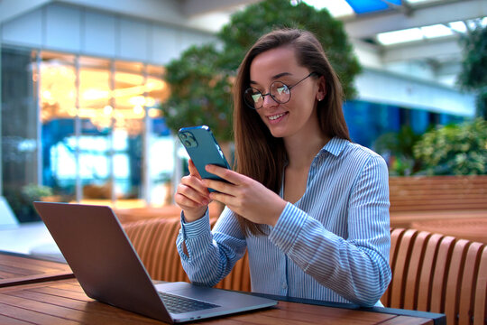 Modern casual smart businesswoman using phone and laptop for remotely working online in a public place