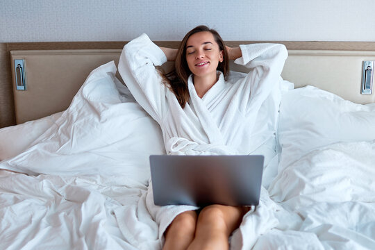Calm smiling dreaming woman freelancer with hands behind head wearing white bathrobe remote working online at a computer on the bed from a hotel room. Easy lifestyle and satisfaction
