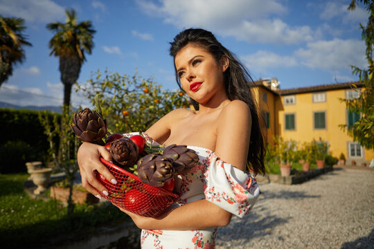 Woman holding basket of vegetables outdoors at her garden. italian life style