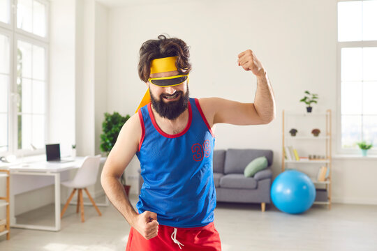 Funny bearded man in colorful sportswear and mask for sleeping making sport workout for muscle power at home. Active lifestyle, funny sport, exercise, workout, training at home concept