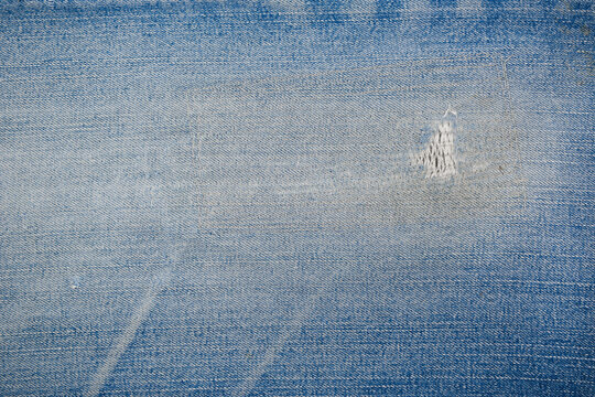 Dirty patch tear Denim jeans textile texture surface for background or wallpaper with copy space. Close up of torn blue jeans fabric pattern design.