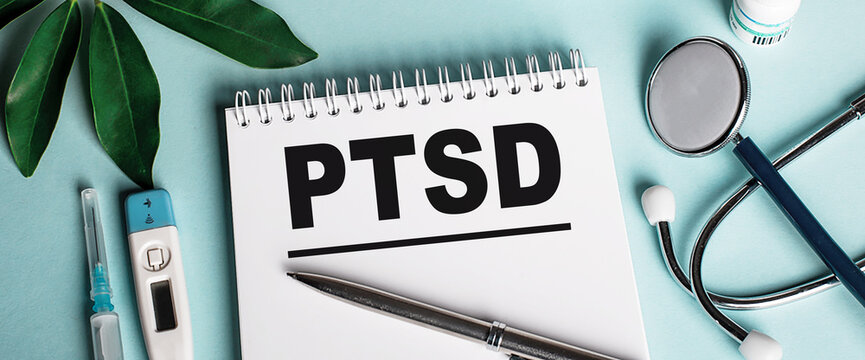 In a white notebook on a blue background, near a sheet of shefflers, a stethoscope, a syringe and an electronic thermometer, the word PTSD is written. Medical concept