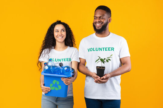Volunteers Holding Plant And Used Plastic Bottles Over Yellow Background