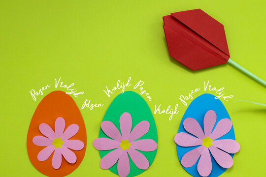 Dutch text Vrolijk Pasen (happy Easter) on a green background with colorful paper eggs, paper flowers and a red paper tulip.
