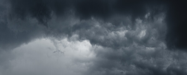 Background of dark stormy ominous clouds in gray moody sky