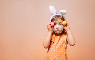 A girl with rabbit ears on her head and a protective mask with painted eggs in her hands on a beige...