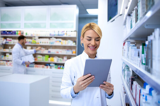 Portrait of female experienced pharmacist working on tablet in pharmacy store by the shelf with medicines.