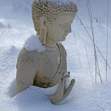 A creme-white buddha statue in winter in a German garden. The buddha has sunken deep in the snow. His hand gesture is still visible.