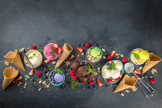 Various colorful ice cream balls in different bowls, with ice cream waffles cones and flavor ingredients - pistachio nuts, berries, lemon, chocolates, vanilla beans, mint. Dark background copy space