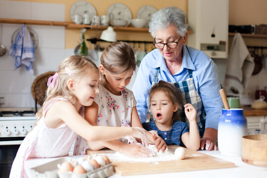 Home cooking. Family and kids make bread for dinner in cozy kitchen. Grandmother and funny little girls preparing homemade food. Children chef concept. Lifestyle authentic moments. Real, true emotions