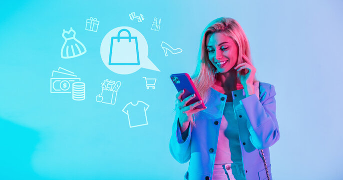 Beautiful happy smiling woman in fashionable clothes holding smartphone and shopping online with shopping icons on blue background. Girl makes purchases on the Internet through the application