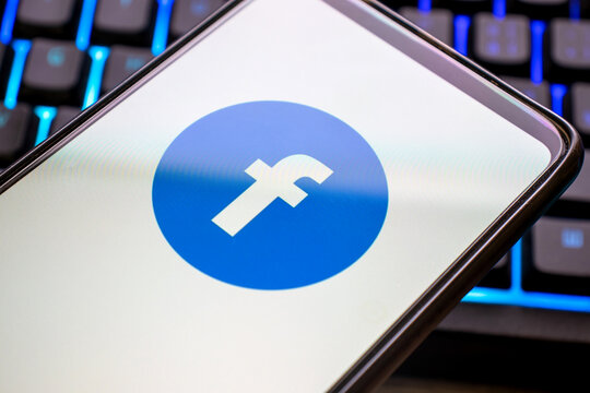 Mobile phone with blue facebook logo on display and colorful illuminated keyboard. Smartphone concept using the messaging application privacy with the symbol on the screen