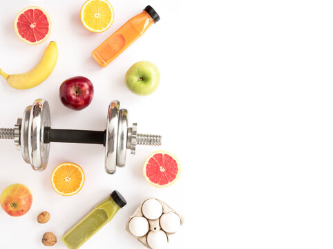 Diet and sports nutrition program. Background with fruits and dumbbells for active weight loss and the result of athletes