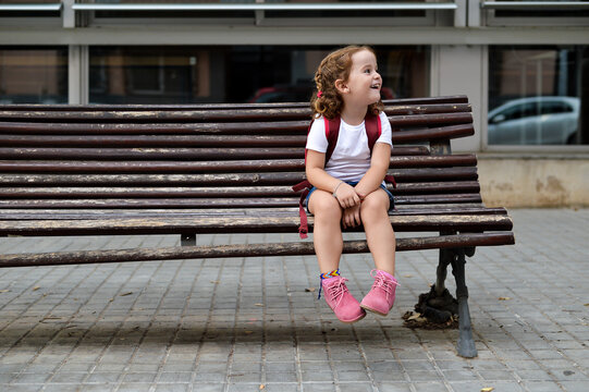Little girl resting in a bench after school