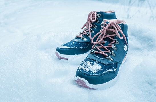 Winter sports footwear - dark blue trekking shoes (boots) outdoor on the snow