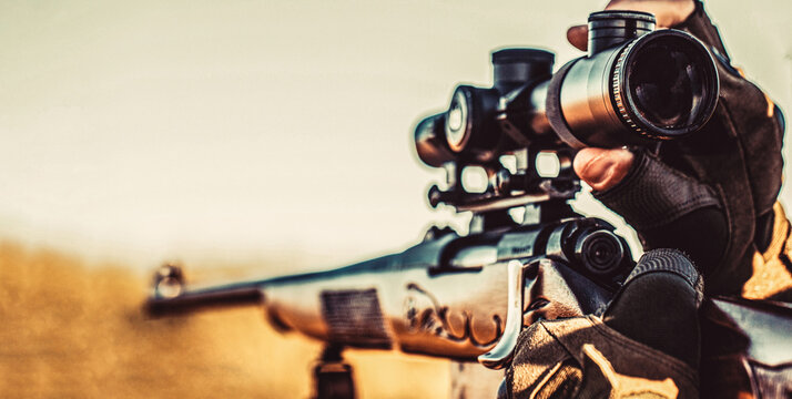 Shooter sighting in the target. The man is on the hunt. Hunt hunting rifle. Hunter man. Hunting period. Male with a gun. Close up. Hunter with hunting gun and hunting form to hunt. Hunter is aiming