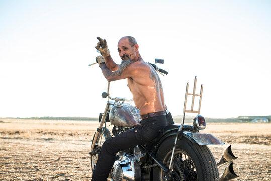 Tattooed motorcyclist aged man