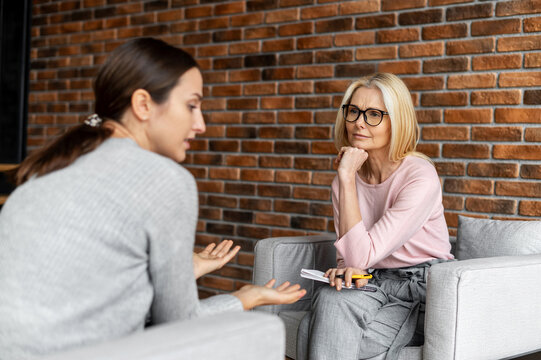 Worried young woman patient sitting at a psychologist's therapist appointment and telling about mental problems, attentive mature female doctor is listening and making notes. Psychotherapy concept