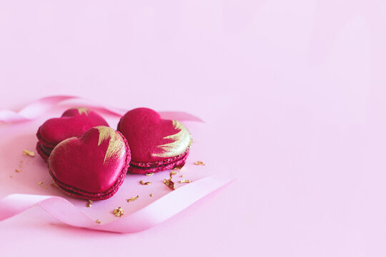 Heart-shaped macaroons with ribbon on a pink pastel background. Concept for Valentine's Day.