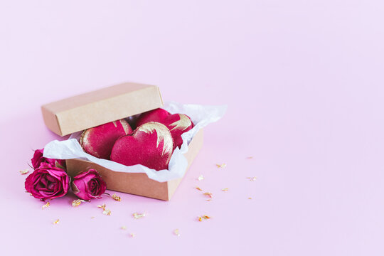 Heart-shaped macaroons in a box on a pink pastel background. Concept for Valentine's Day.