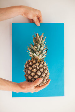 Male hand holding pineapple in front of a white wall