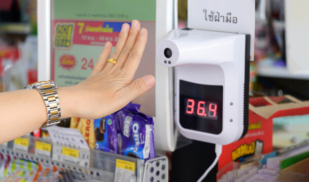 Samut Sakhon, Thailand - November 13,2020 : Focus at female customer hand measuring body temperature with non-contact infrared thermometer in convenience store
