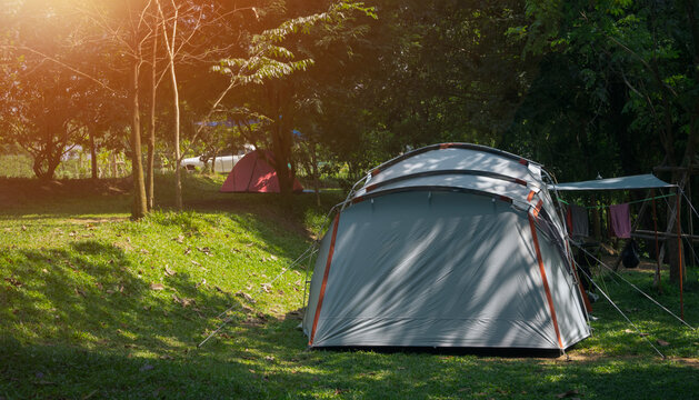 Sunlight and shade on surface of field tents on green lawn in camping area at natural parkland