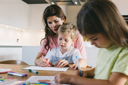 Young Caucasian Mother Drawing With Her Son and Daughter at Kitchen Table