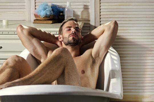 Man with muscular legs in bath. Hygiene, grooming, health. Sexy gay relax naked in bathtub in bathroom. Bath, bathing, shower and spa.