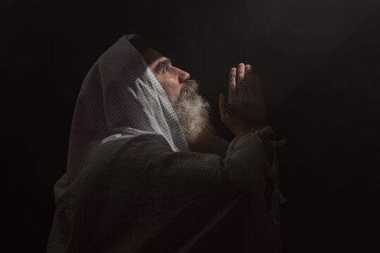 A senior man standing in dark smoky background light ray from above. Prayer gesture.