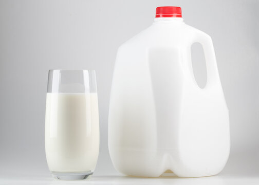 Milk. Glass of milk and one gallon of whole milk. Organic milk product. White plastic bottle one gallon or 3.78 liter on white background.