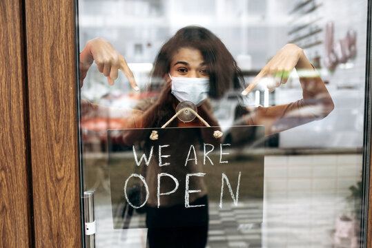Curly female African American small business owner in medical mask points at a signboard WE ARE OPEN at the entrance to a restaurant, bar, cafe or shop, and waiting for visitors