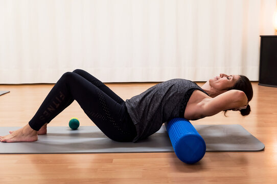 Woman doing abdominals on a foam roller in gym