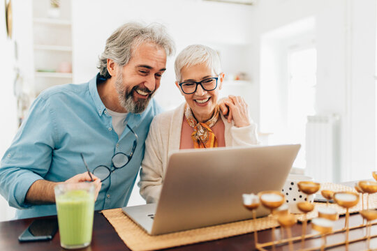 Senior couple using laptop at home for video call, shopping ,reading news