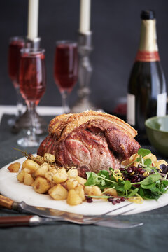 Roast shoulder of pork,with sauteed rosemary potatoes and a pomegranate and herb salad on a marble serving board.