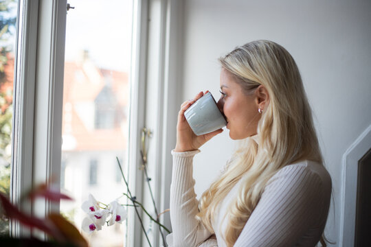 Beautiful girl sips tea from her mug in winter. She's near the window and it's cold outside. Indoor lifestyle concept