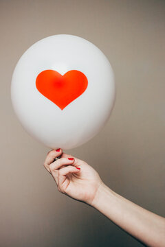 Hand holding a white balloon with a heart