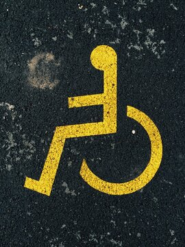 Yellow parking space for disabled sign on black asphalt