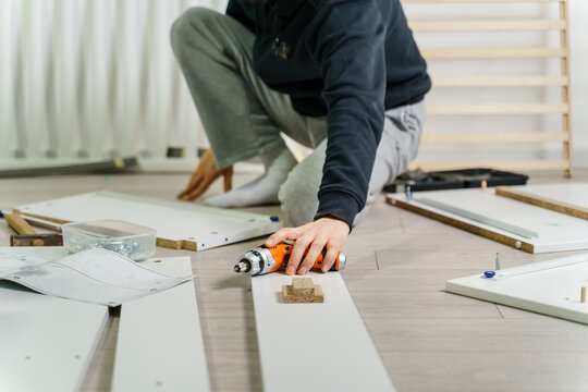 One unknown Man alone Putting Together Self Assembly Furniture sitting on the floor at Home holding electric screwdriver looking the instructions - side view DIY concept real people copy space