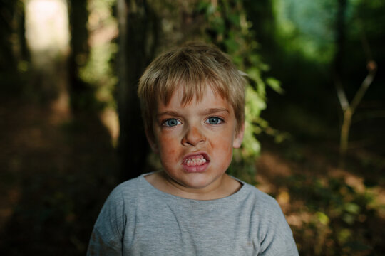 Boy covered in red clay dust bares his teeth while pretending to be a tiger in a forest.