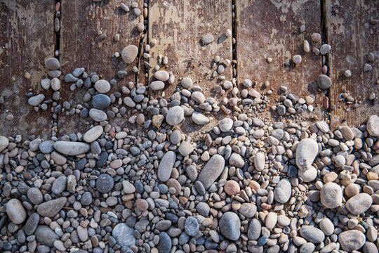 A patter of mixed beach stones laying over a wooden background