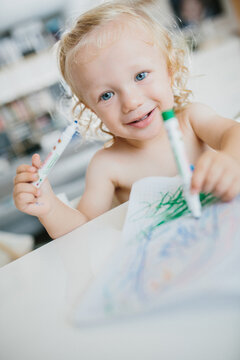 Cute blond toddler coloring a book with colored pens