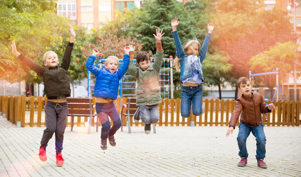 Happy kids jump and play outside. High quality photo